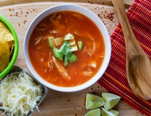 Chicken tortilla soup with tortilla chips, cheese, lime garnish and wooden spoon.