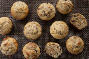 Eleven freshly baked raisin bran muffins on a brown mat.