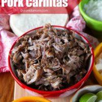 A red serving bowl full of baked pork carnitas.