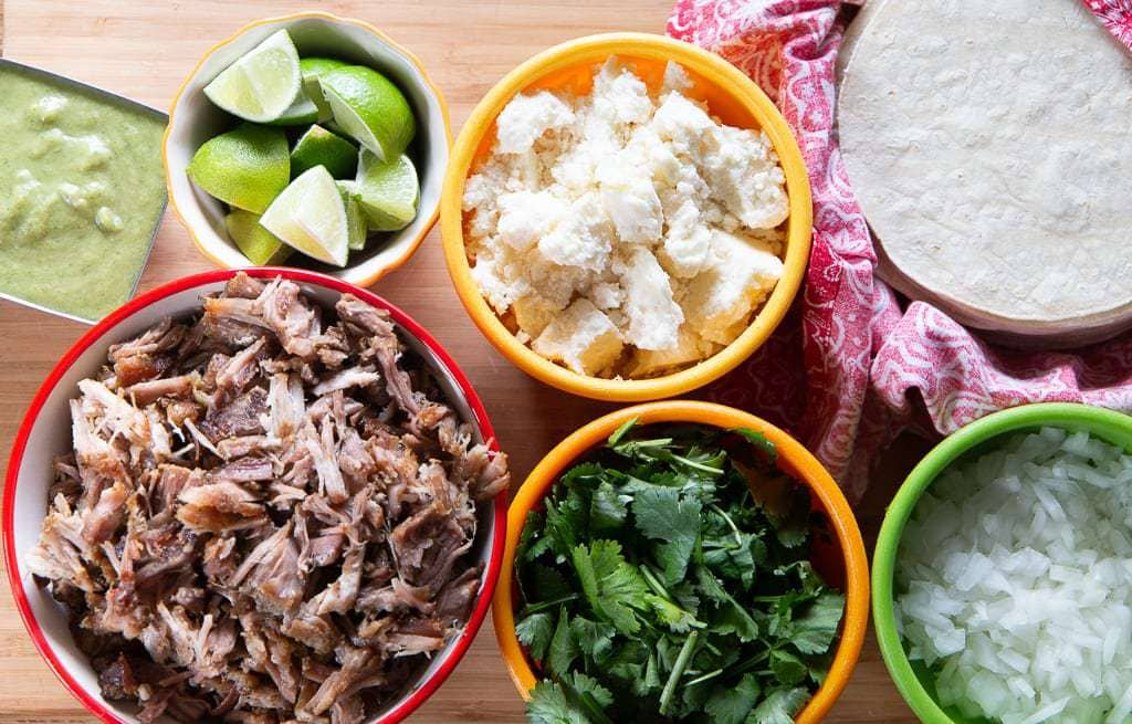 carnitas with garnishes- tortillas, cheese, lime, cilantro and onion