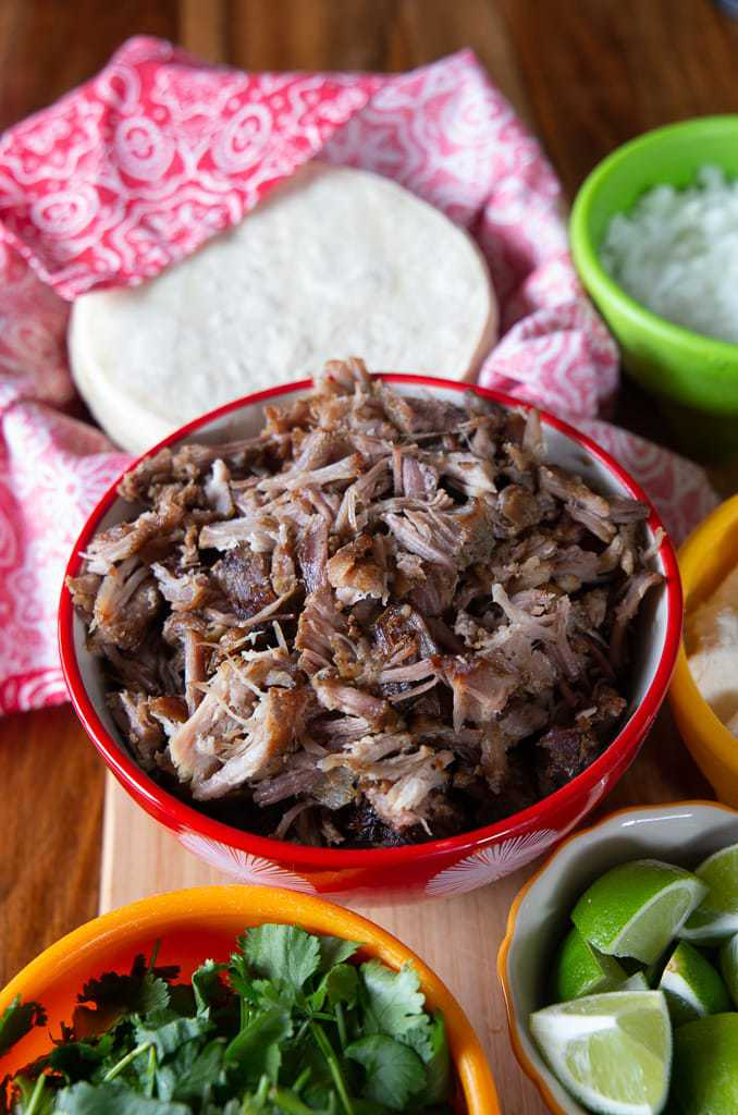 Mexican shredded pork in bowl with white corn tortillas