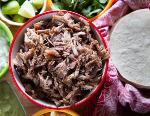 Mexican shredded pork with tortillas, lime, onion and cilantro garnish.