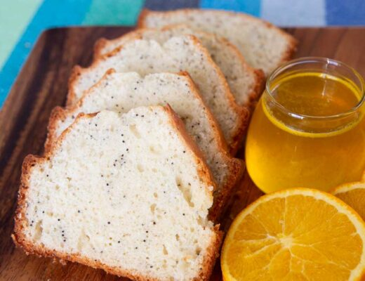 Close up of sliced poppy seed bread with orange glaze.