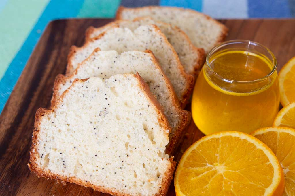 Close up of sliced poppy seed bread with orange glaze.
