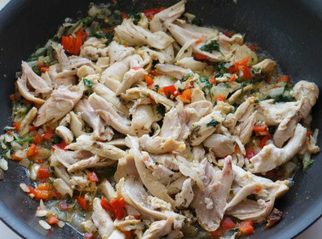 Chicken slices, herbs, diced onions, and peppers frying in a pan.