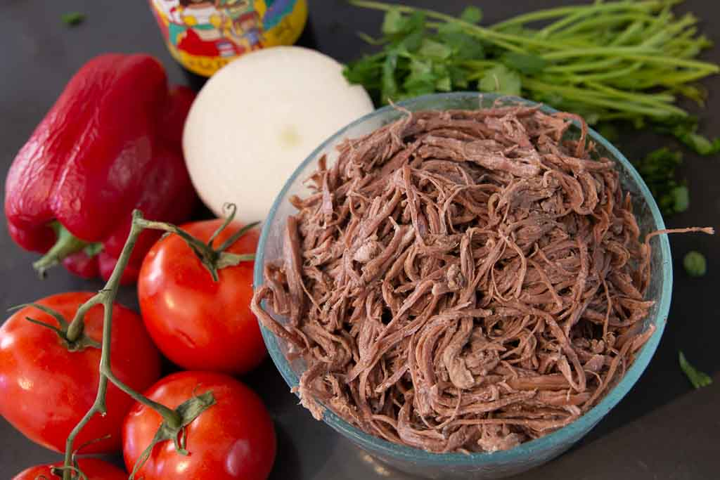 Glass bowl of shredded beef centered to the right and flanked by vegetables.