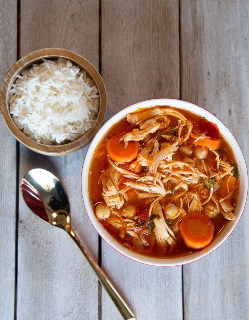 costa rican garbanzo soup with chicken and tomato, spoon, and cooked white rice