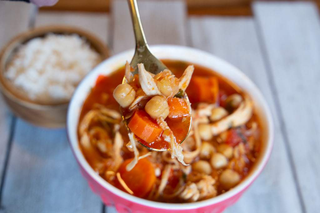 bowl of chicken garbanzo bean soup with dish of white rice