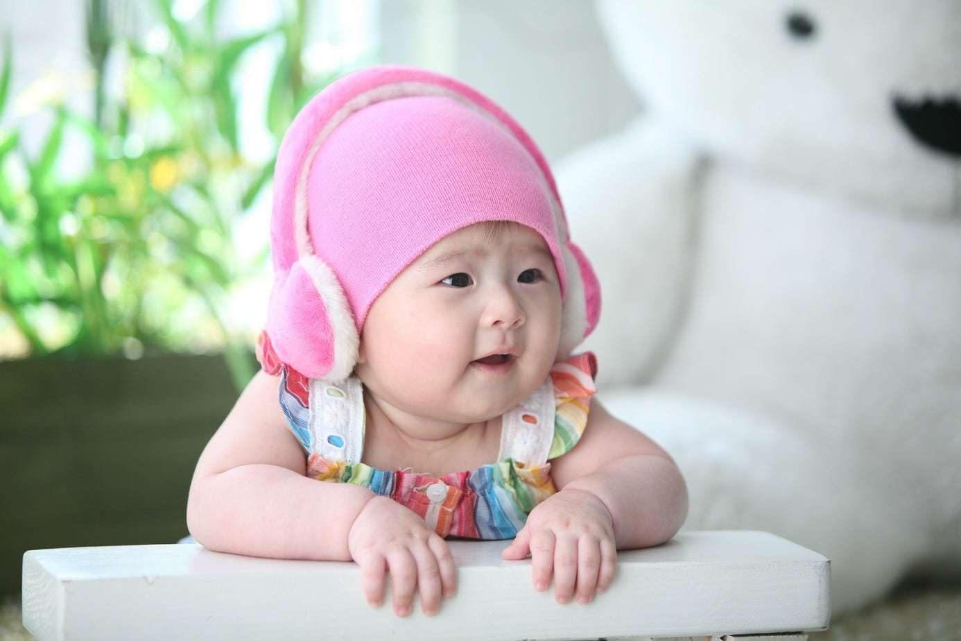 baby with pink headphones listening to kids spanish songs