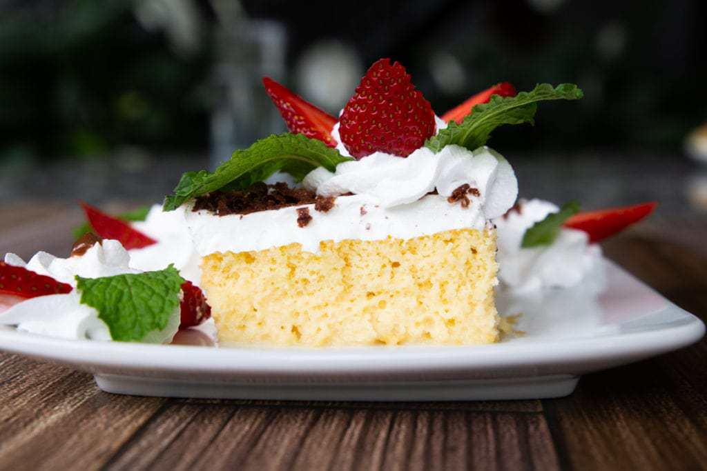 Cross section of Costa Rican moist cake topped with strawberries and mint.