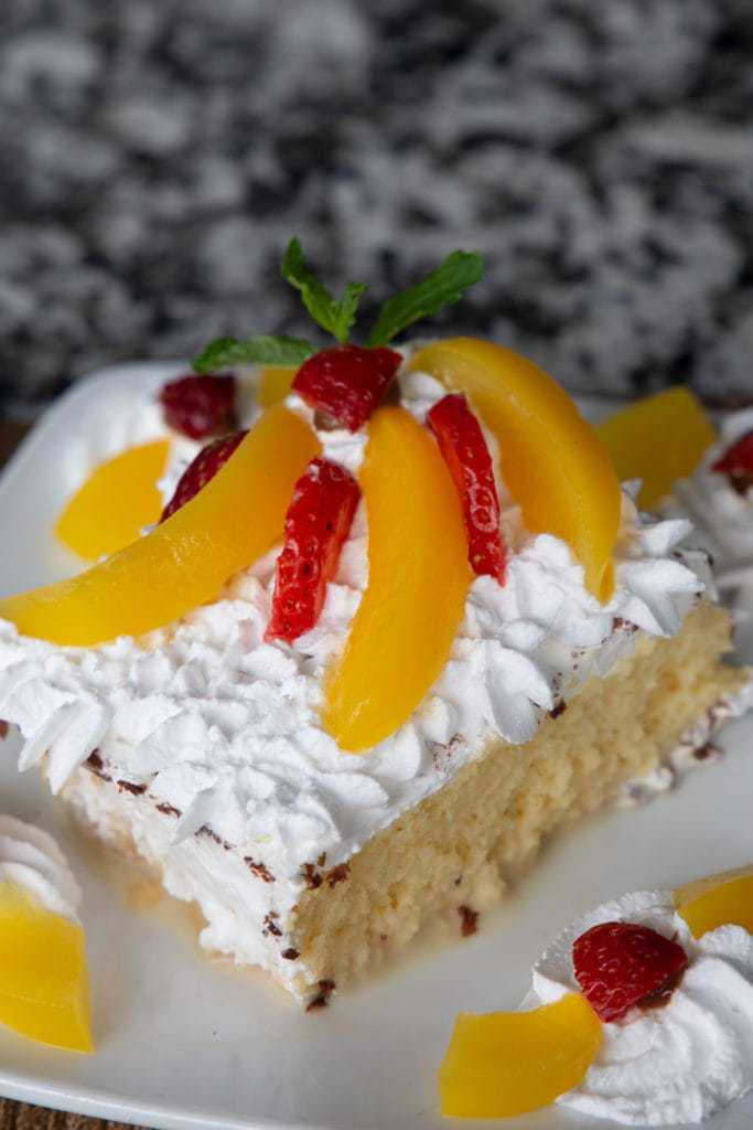tres leches cake topped with peach slices and strawberries