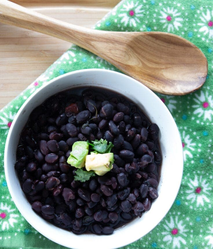 White ceramic bowl of Costa-Rican style slow cooked black beans topped with diced avocado and cilantro leaves.