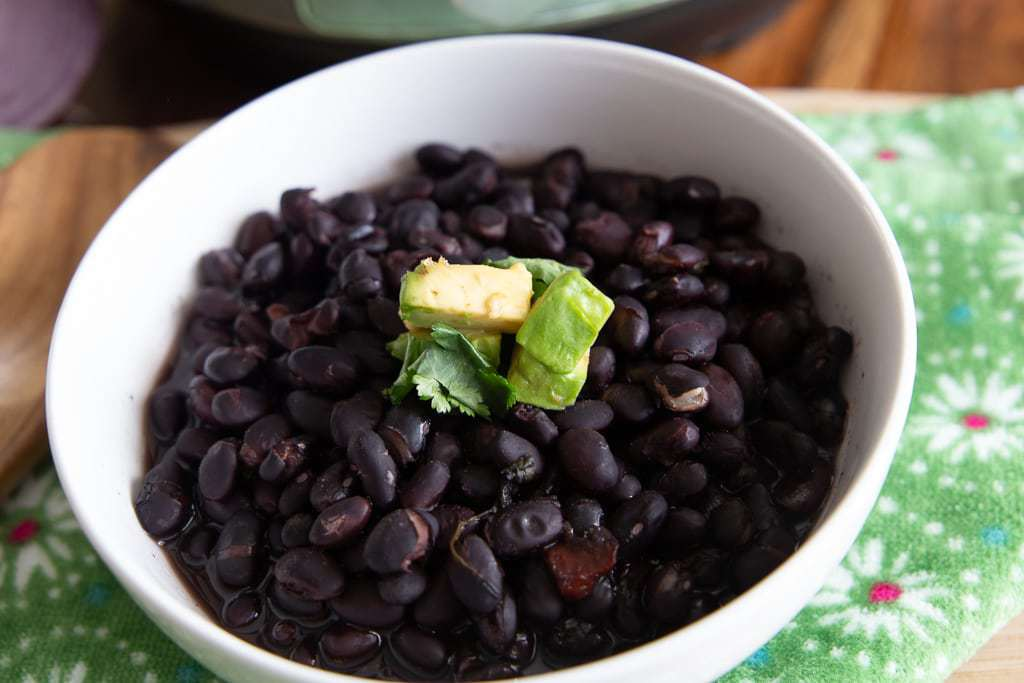 cooked black beans with avocado garnish