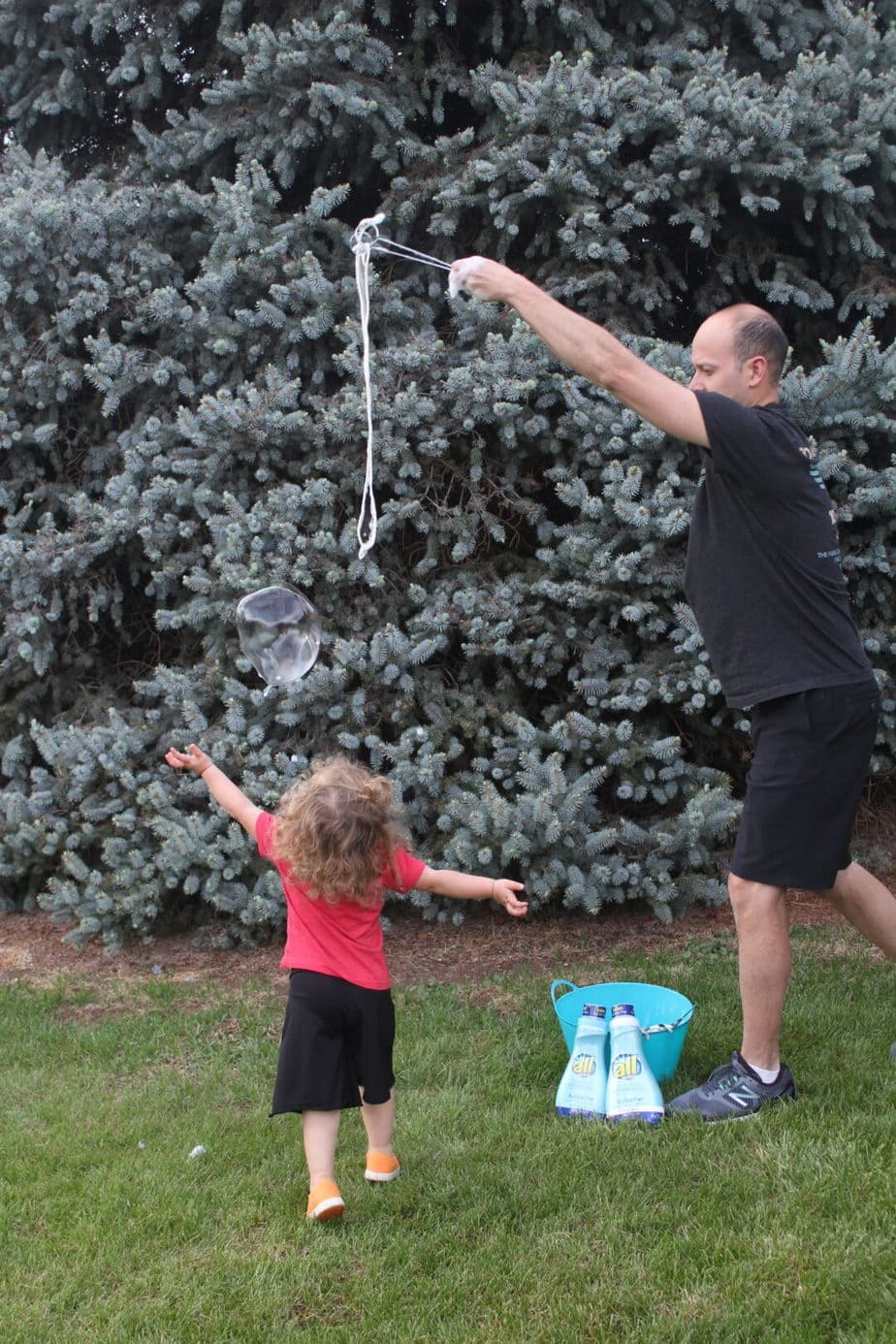 Toddler girl popping giant bubble with dad in front of a pine tree.