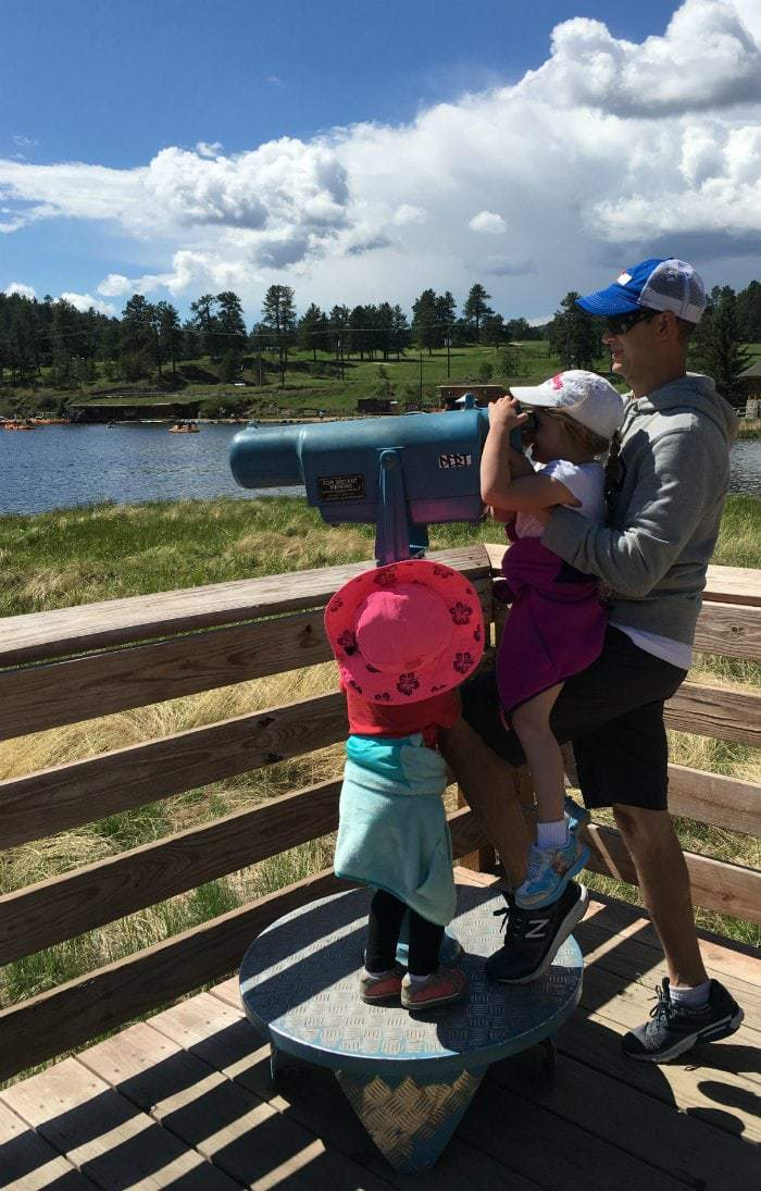 Father and young daughters looking out onto evergreen lake at an observation station.