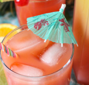 Rum punch cocktail in glass with ice and umbrella.