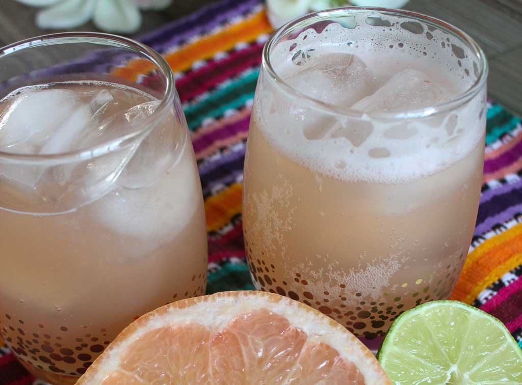 Close-up of two skinny paloma margarita drinks placed upon a striped cloth.