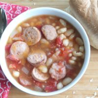 Slow cooker sausage and white bean soup serving in a ceramic bowl.
