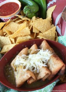 Series of chile rellenos topped with shredded cheese in a red bowl surrounded by fresh tortilla chips.