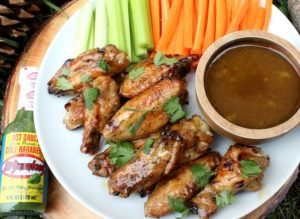 Mango glazed chicken wings piled on a plate with a small bowl of dip and sliced vegetables.