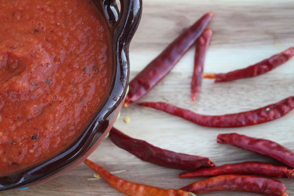 Close-up of chile del arbol salsa in a black ceramic container.