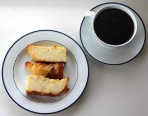 Three slice of tamal de masa alongside a cup of black coffee.