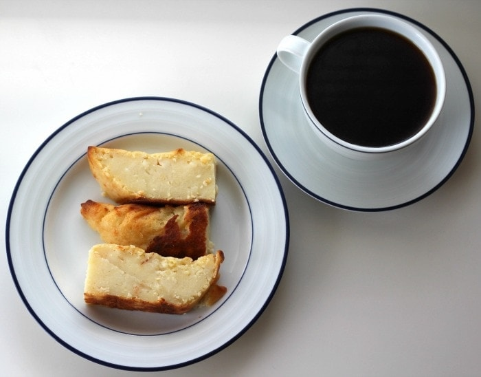 Three slice of tamal de masa alongside a cup of black coffee.