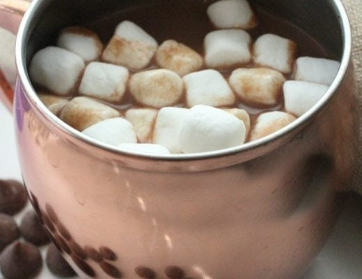 Rose gold mug of hot chocolate topped with mini marshmallows.