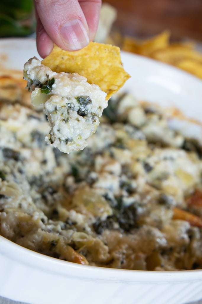 tortilla chip above warm spinach artichoke dip