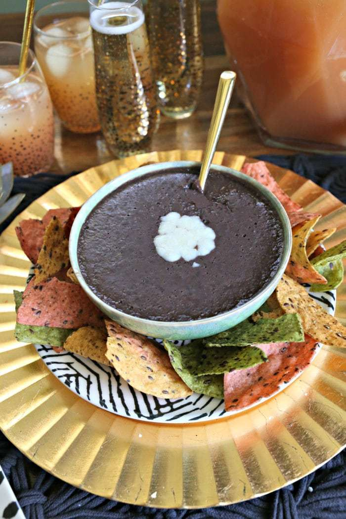 black bean dip topped with cheese on a gold plate served with tri color tortilla chips