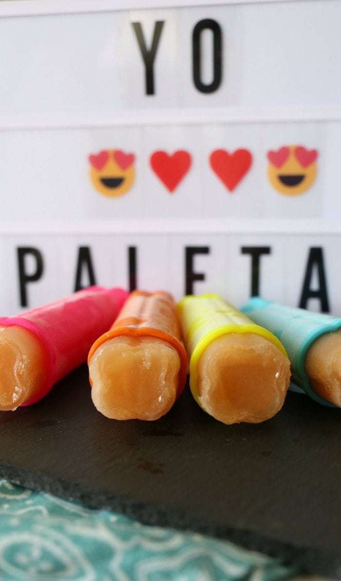 Ginger and guava paletas encased in pink, orange, yellow, and blue tubes.