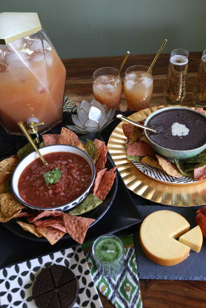 bean dip on table with guava cocktail, red salsa and cheese wheel