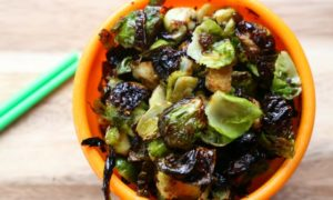 Crispy sugar free Asian Brussels sprouts in an orange bowl.