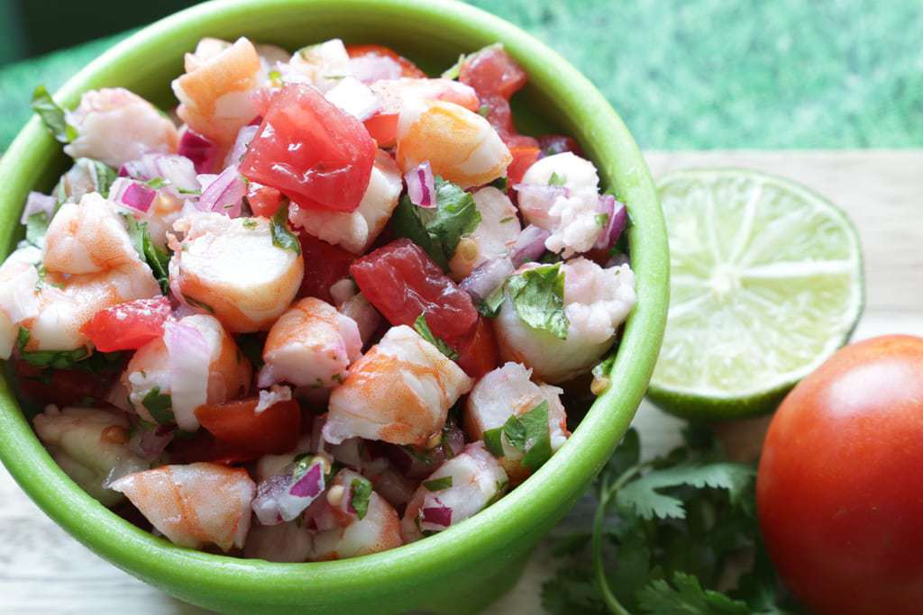 lime and tomato on cutting bowl with bowl of ceviche