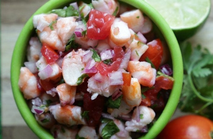 Shrimp ceviche piled in a green bowl.