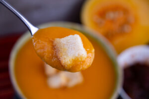 Silver spoon filled with butternut squash soup and a crouton.