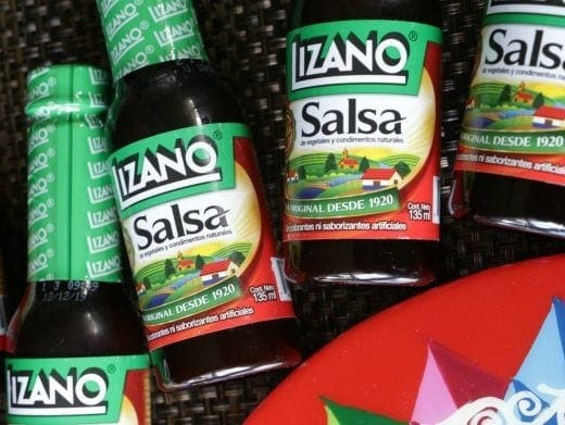 Bottles of Salsa Lizano lined up on a woven black mat.
