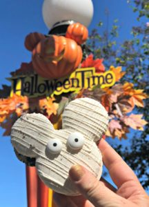 Mickey Mummy Macaron held up in front of Disney's Halloween Time sign.