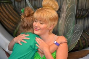 Young girl getting a hug from Tinker Bell at Disneyland.