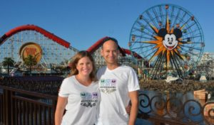 Couple posing in front of a Disney amusement park.