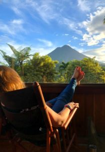 Woman relaxing in a chair overlooking Arenal Volcano Costa Rica.