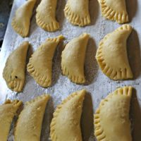 Series of crimped and unbaked empanadas on a baking sheet.