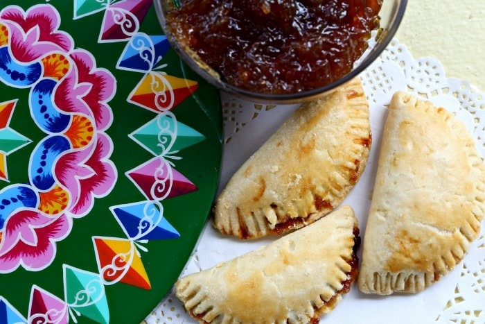 Three baked chiverre empanadas arranged on a doily.