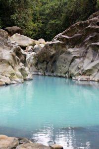 Aquamarine pool surrounded by boulders, Bajos del Toro Costa Rica.