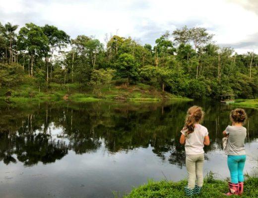 children standing by cristalline lake