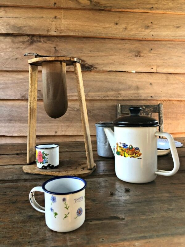 Coffee straining device, coffee pot, and two porcelain mugs with wildflowers painted on them.