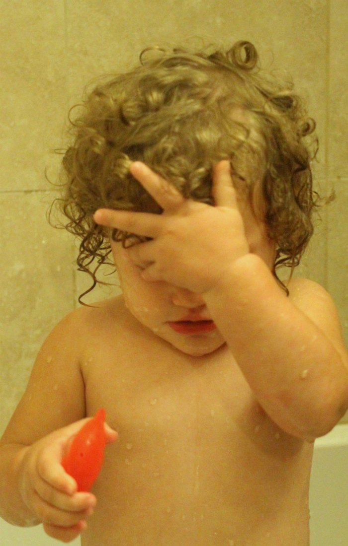 toddler with hand on head in bath tub