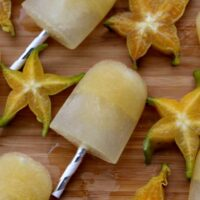 Starfruit popsicles on wooden cutting board with yellow 5 pointed carambola fruit