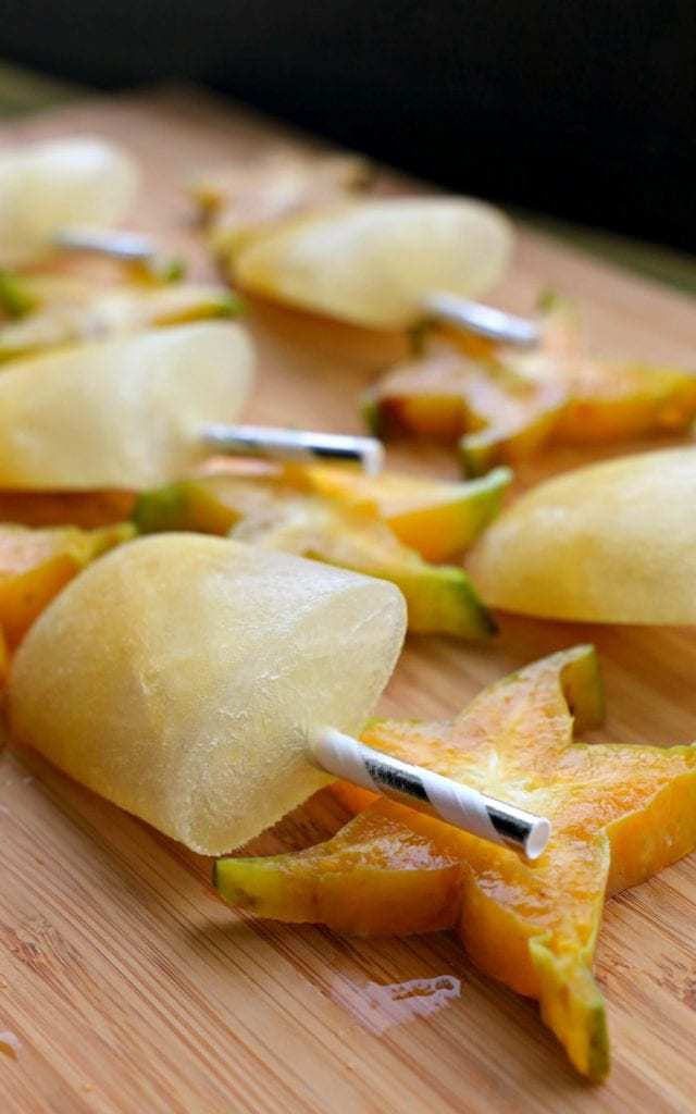 Frozen starfruit popsicles and starfruit halves arranged on a wooden cutting board.