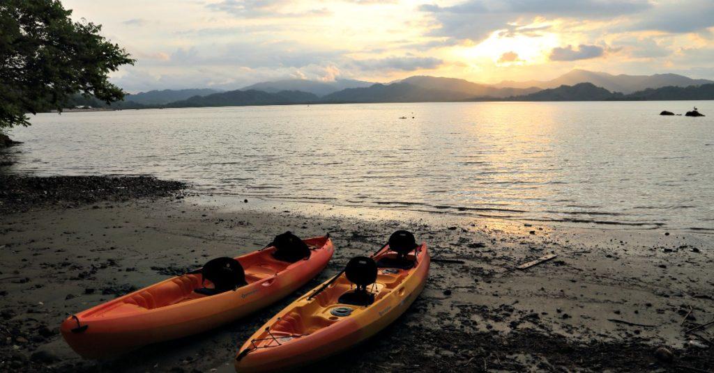 Two orange kayaks on bay in Costa Rica at sunset.